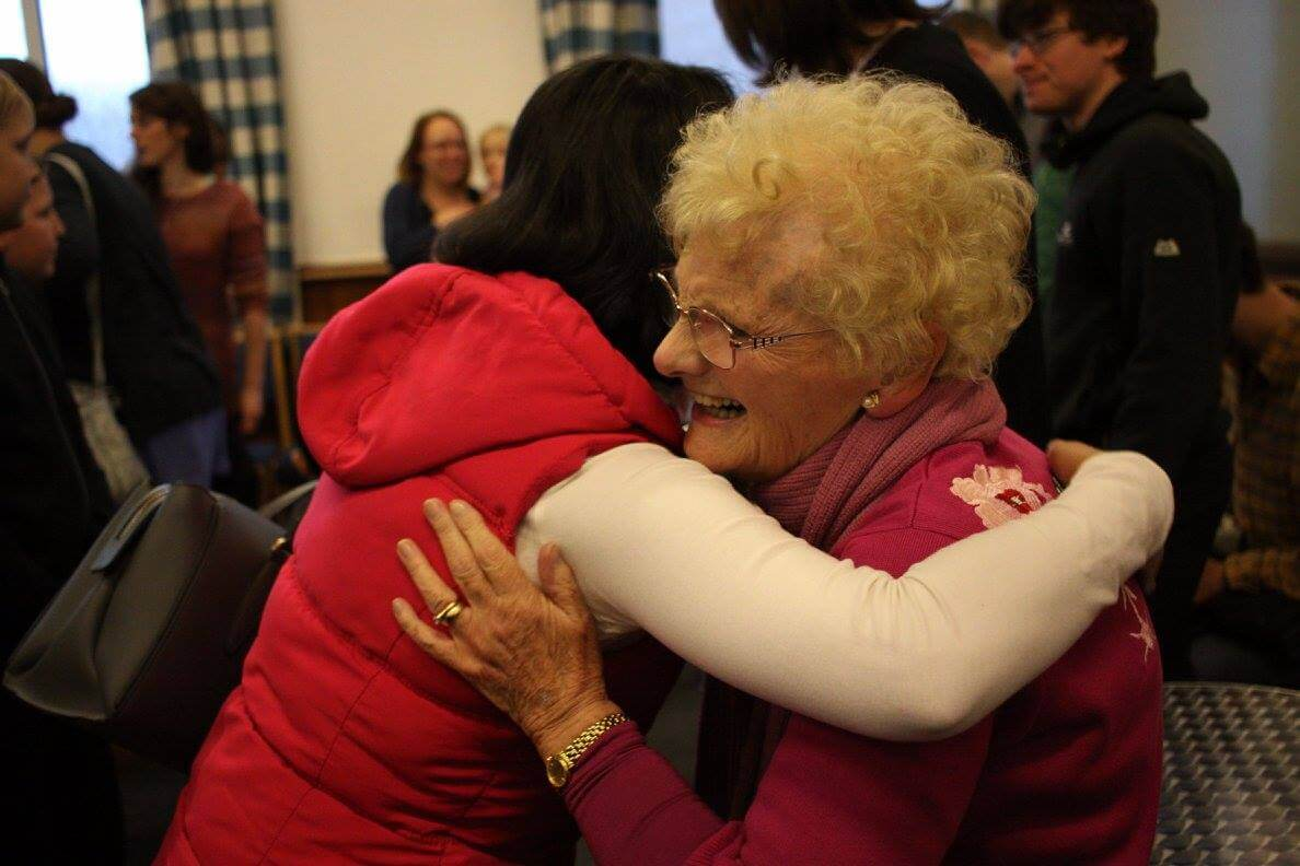 Two women embracing each other in a room full of people